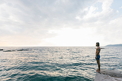 Man standing on edge of sea - p429m2202357 by Sofie Delauw