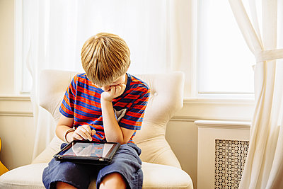 Caucasian boy using digital tablet in living room - p555m1408613 by Inti St Clair photography