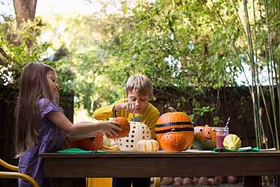 Boy and sister carving pumpkins on garden table - p924m1468978 by Kinzie Riehm