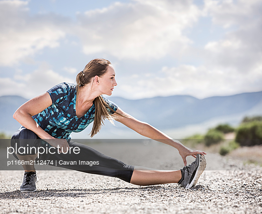 Full length of confident woman stretching leg while exercising on road against cloudy sky - p1166m2112474 by Cavan Images