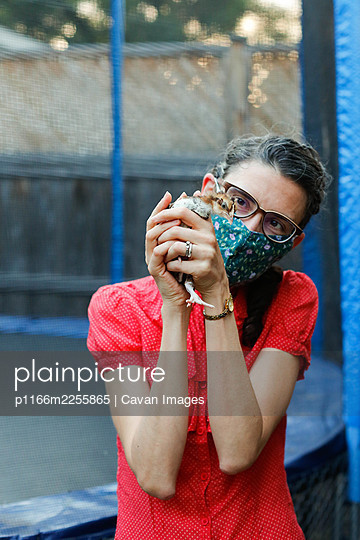 Woman holding a chicken in an urban backyard - p1166m2255865 by Cavan Images