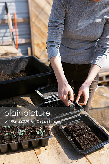 A young female farmer preparing soil blocks for her flower seeds - p1166m2269676 by Cavan Images