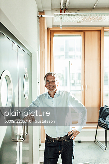 Smiling male business professional leaning on closed window in office - p300m2265710 by Gustafsson