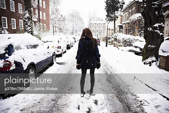 Girl on snowy street - p378m795845 by Jamie Stoker