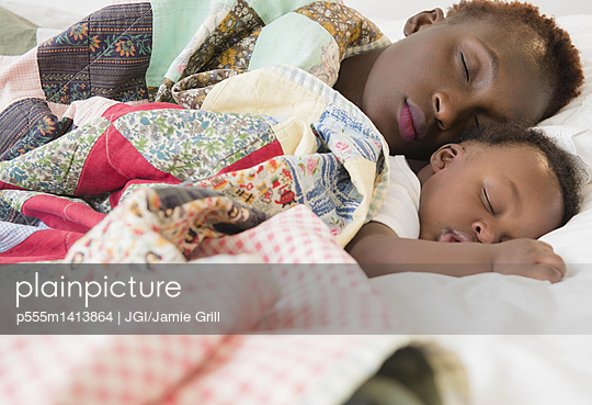Black mother and son sleeping on bed - p555m1413864 by JGI/Jamie Grill
