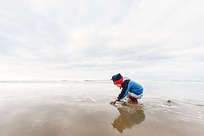Preschooler playing at beach in winter - p1166m2171915 by Cavan Images