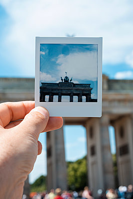 Man holding a polaroid of the Brandenburg Gate in Berlin, Germany - p1423m2210325 by JUAN MOYANO