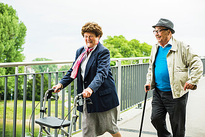 Senior couple with walking stick and wheeled walker - p300m1047405f by Uwe Umstätter