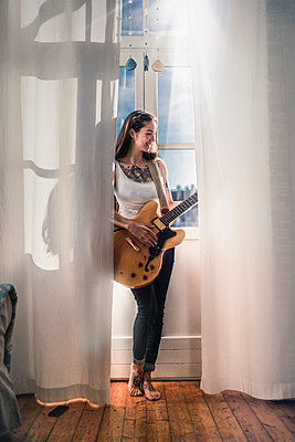 Happy young woman standing at the window at home with a guitar - p300m2132395 by Richárd Bellevue