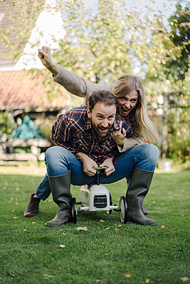Laughing couple pretending to ride a toy car in the garden - p300m2166690 by Kniel Synnatzschke
