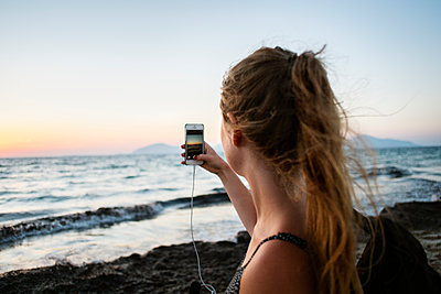 Greece, Kalymnos, Young woman photographing sunset sky with smart phone - p352m1186953 by Lena Katarina Johansson