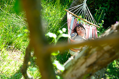 Young woman sleeping in hammock - p427m2203622 by Ralf Mohr