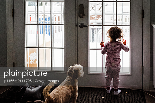 Little girl and dog looking out window at snow - p1166m2111725 by Cavan Images