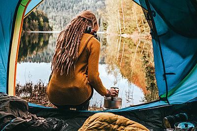 Frau mit Kaffee sitzt vor ruhigem Bergsee - p1455m2204904 von Ingmar Wein