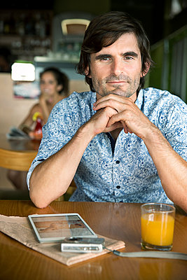 Portrait of a man waiting in a cafe - p300m1028830f by Tomas Rodriguez