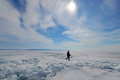 Russia, Lake Baikal, man walking on frozen lake - p300m1053012f by Gerald Nowak