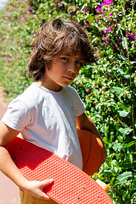 Close-up of boy with basketball and skateboard standing by plants in park - p300m2203052 by Valentina Barreto
