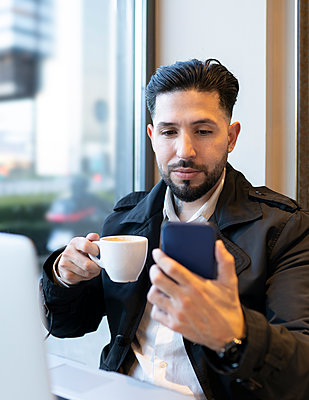 Male entrepreneur holding coffee cup during video call in cafe - p300m2266368 by Jose Carlos Ichiro