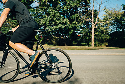 Low section of sportsman cycling on road during sunny day - p426m2270827 by Maskot