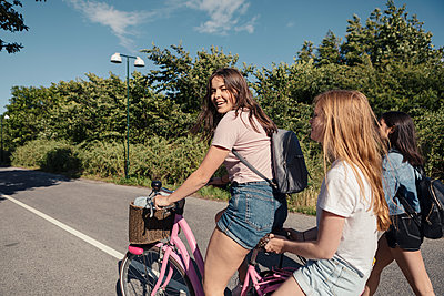 Female teenagers cycling on street during sunny day - p426m2270945 by Kentaroo Tryman
