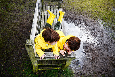Overhead view of baby boy and brother in yellow anoraks on park bench - p429m1408106 by Bonfanti Diego