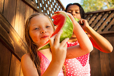 Two girls eating slices of watermelon in garden - p924m947154f by Kevin Kozicki