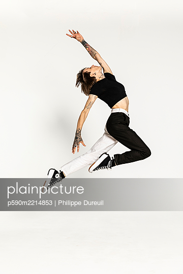 Jumping tattooed dancer with arched back - p590m2214853 by Philippe Dureuil