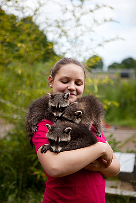 Girl with three racoons - p1195m1071095 by Kathrin Brunnhofer