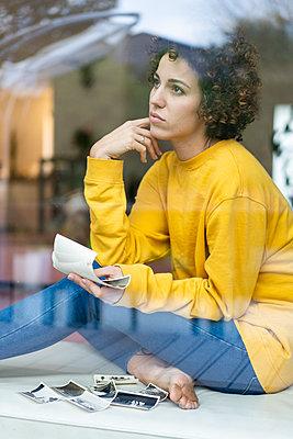 Serious woman sitting behind window at home holding photos - p300m2080289 von Joseffson