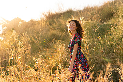 Happy young woman standing in summer meadow - p300m2102544 by VITTA GALLERY