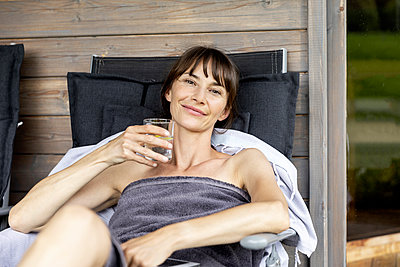 Portrait of woman relaxing on a lounge holding glass of water - p300m2131870 by Jo Kirchherr