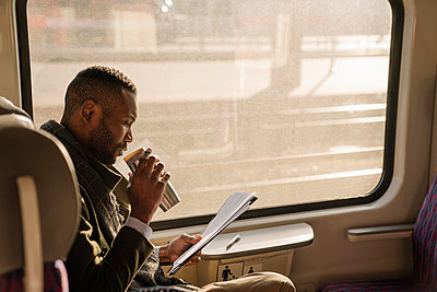 Stylish businessman with reusable cup and documents in a train - p300m2154587 by Hernandez and Sorokina