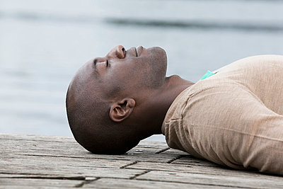 Man napping on decking by lake - p301m844122f by Paul Hudson