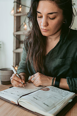 Woman taking notes in her diary - p312m2191297 by Rania Rönntoft