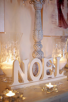 Lit candles with crystal glassware and lettering on painted tabletop - p349m789730 by Brent Darby