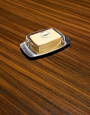 Butter in dish on wooden table - p42919255 by Steve Gallagher Photography