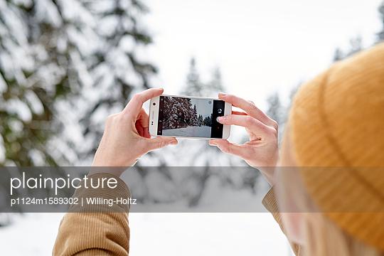Frau macht ein Foto von schneebedeckten Bäumen - p1124m1589302 von Willing-Holtz