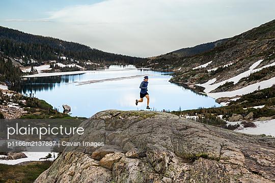 Man trail runs on rock over lake in Indian Peaks Wilderness, Colorado - p1166m2137887 by Cavan Images