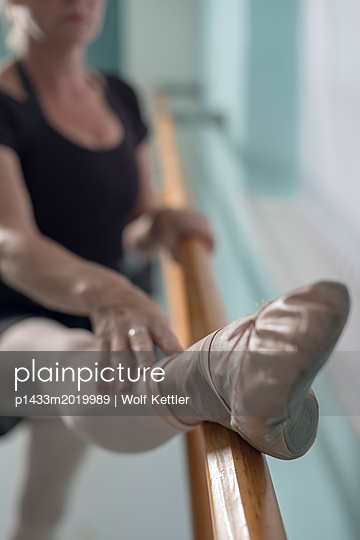 A female ballet dancer warms up at the barre. - p1433m2019989 by Wolf Kettler