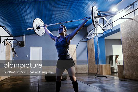 Woman lifting barbell in gym - p300m1581598 von Zeljko Dangubic