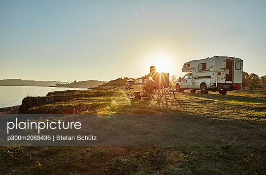 Chile, Talca, Rio Maule, camper at lake with woman and dog at sunset - p300m2069436 by Stefan Schütz