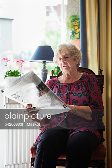 Relaxed senior woman reading newspaper at home