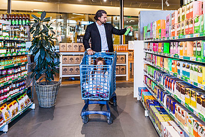 Girl sitting in cart while father shopping in supermarket - p1264m1173208 by Astrakan