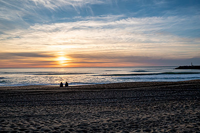 Two people on the beach sand looking at the ocean at sunset - p1487m2108715 by Ludovic Mornand