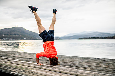 Athlete doing a headstand on wooden deck at the lakeshore - p300m1581149 von Daniel Waschnig Photography