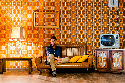 Man sitting on couch in vintage living room - p300m2069888 by Giorgio Fochesato