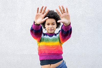 Girl with hand raised standing against gray wall - p300m2251963 by Jose Carlos Ichiro