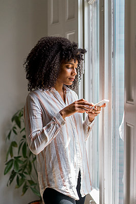 Beautiful female entrepreneur using smart phone while standing near window in office - p300m2264480 by VITTA GALLERY