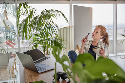 Businesswoman holding coffee cup while doing business plan at desk in office - p300m2266052 by Jo Kirchherr
