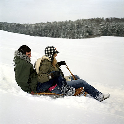 a teenage couple sledging - p3160898f by Kalle Singer